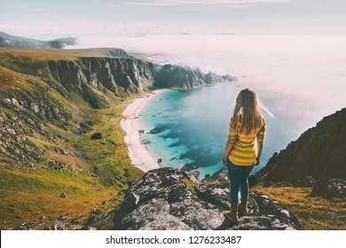 Summer travel woman tourist standing alone on mountain top over sea beach active lifestyle hiking adventure vacations in Norway outdoor