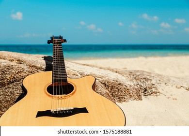 Summer traveling with guitar on beach background, resting on rocks. tropical beach. blue sky. Summer vacation concept. copy space