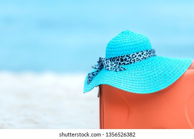 Summer traveling with old suitcase and Fashion woman, fish star, sun glasses, hat. Travel in the holiday, blue sky and beach background. Summer and Travel Concept