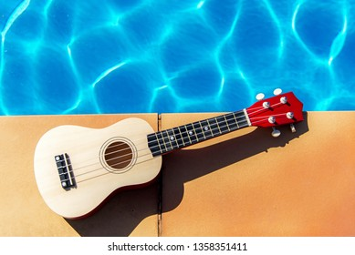 Summer Traveling ukulele near swimming pool at the texture blue water background