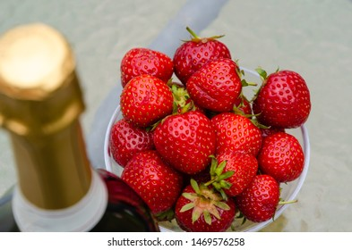 Summer treat with a fresh strawberries and the top of a blurred bottle sparkling wine on a table