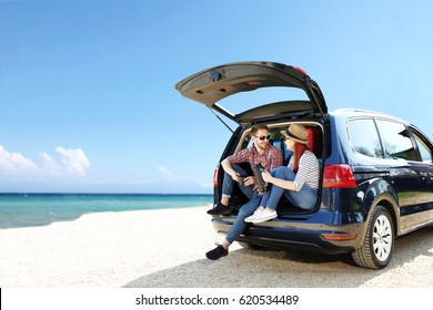 Summer trip on beach by car and two lovers