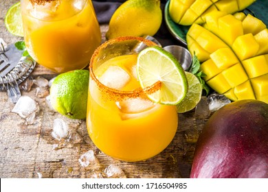 Summer tropic mexican cold cocktail. Mango margarita cocktail, with tequila, lime, lemon, hot chili jalapeno peppers. Wooden background with bar party utensils copy space