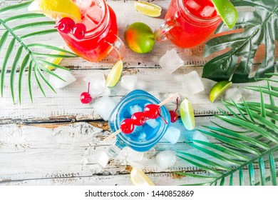 Summer tropical cold drinks. Blue Hawaiian, Tequila sunrise, Sea breeze cocktails over light blue wooden beach background, copy space
