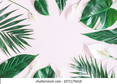 Summer tropical composition. Green tropical leaves and white flowers on pink background. Summer concept. Flat lay, top view, copy space