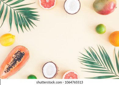 Summer tropical composition. Green palm leaves and tropical fruits on pastel yellow background. Summer concept. Flat lay, top view, copy space
