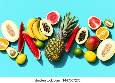 Summer tropical fresh fruits flat lay minimalist background with strong contrast sunny shadow