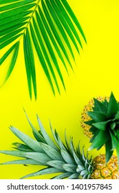Summer tropical fruit composition. Tasty pineapples decorated palm leaves on yellow color background, flat lay.