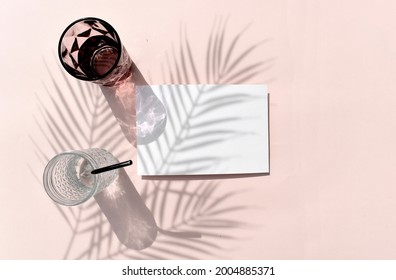 Summer tropical mockup still life flat lay. Empty blank invitation card, cocktail glass on beige background. Palm leaves shadow. Reflection. Eco minimal concept for wedding, vacation or relax.