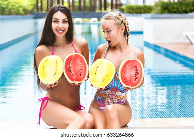 Summer tropical portrait of two pretty young girls having fun near pool, holding two big watermelons near boobs, surprised grimaces, crazy emotions, bright bikinis, enjoy vacation.