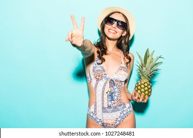Summer tropical positive portrait of young pretty woman having fun, wearing bright bikini holding pineapple on green