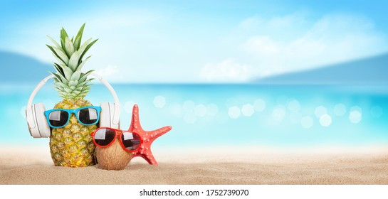 Summer tropical sea with sparkling waves, pineapple and coconut with sunglasses and headphones on hot sand beach. Travel and vacation concept with copy space