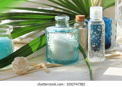 Summer tropical spa body and beauty treatment set on sunny bathroom shelf. Blue glass jars of sea salt, facial toner, green fresh palm leaf.