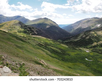 Summer in the tundra in Rocky Mountains National Park in Colorado.White puffy clouds cast shadows on the land below.