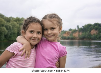 In summer two small beautiful laughing girlfriends stand embracing on the river bank.
