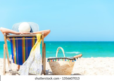 Summer Vacation. Asian lifestyle healthy woman relaxing and happy on beach chair with cocktail coconut juice in holiday summer.  Chill and Freedom outdoor in the summertime.  Travel and lifestyle