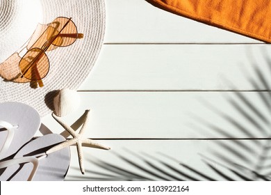 Summer vacation background of beach accessories:  sun hat, flip flops, towel,  shells and shadow of tropical palm leaves. Vacation, holiday, travel, tourism, summertime concept. Top view.