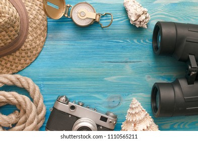 Summer vacation background with copy space. Hat,  photo camera, compass, binoculars, rope and seashells on blue wooden table background.