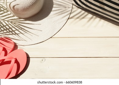 Summer vacation background of straw hat, beach bag, pink flip flops and palm leaves shadow. Vacation, holiday, travel, tourism concept. Top view.