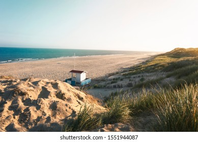 Summer vacation at the beach in the morning light with beach, marram grass, dunes, lifeguard house and sea, on Sylt island, Germany, at the North Sea