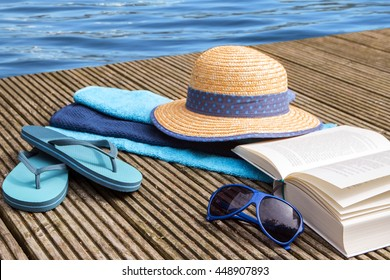 summer vacation, blue water and accessories for beach holidays as straw hat, flip flops,  sunglasses, towels and a book on a wooden jetty at the pool, selected focus and narrow depth of field