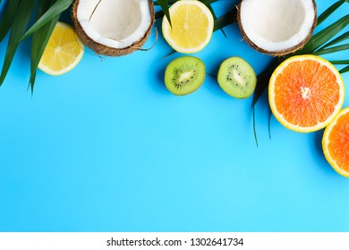 summer vacation, cocktail, tropical beach. creative layout of exotic fruits, banner, poster template with copy space for text design. palm leaves, lemon, orange, kiwifruit, coconut on blue background