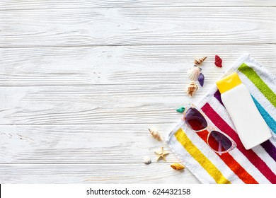 summer vacation concept flat lay. colorful towel, sunglasses, yellow sunscreen and star shells on white rustic wooden background, top view. space for text. travel and summer holiday
