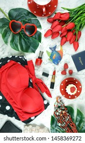 Summer vacation concept flatlay with red feminine accessories on white marble background.