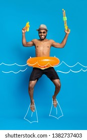 Summer vacation concept. Happy african american guy in swimwear and inflatable ring jumping with water guns like floating in water, drawn waves and flippers