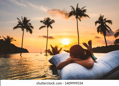Summer vacation concept, Silhouette asian woman with bikini relax in infinity pool hotel resort with sea beach and palm tree background at sunset in Koh Kood, Thailand