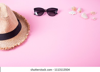 Summer and vacation concept. Top view of beach accessories - sunglasses, straw hat and shells on pink pastel background.
