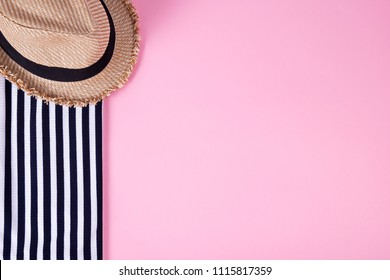 Summer and vacation concept. Top view of striped clothes and straw hat on pink pastel background.