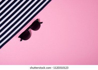 Summer and vacation concept. Top view of striped clothes and sunglasses on pink pastel background.