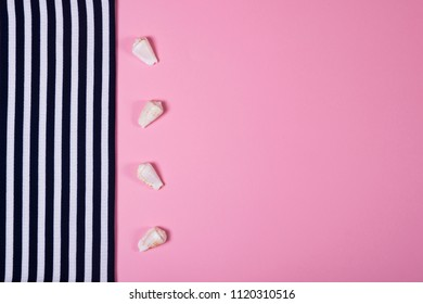 Summer and vacation concept. Top view of striped clothes and four seashells on pink pastel background.