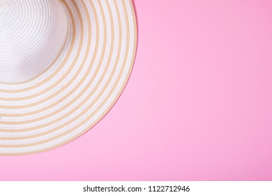 Summer and vacation concept. Top view of Straw striped hat on pink pastel background. Flat lay.