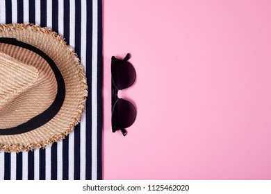 Summer and vacation concept. Top view of striped clothes, sunglasses and straw hat on pink pastel background.