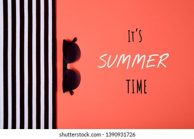 Summer and vacation concept. Top view of striped clothes and sunglasses on coral color background with inscription It's summer time. Fasionable concept. Color of the year 2019.