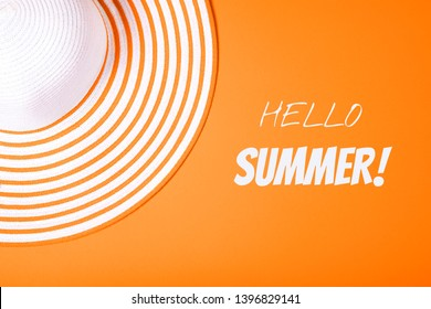 Summer and vacation concept. Top view of Straw striped hat on russet orange color background with inscription Hello Summer. Happy Summer time. Color of the year 2019.. Fasionable concept.