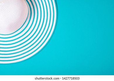 Summer and vacation concept. Top view of Straw striped hat on blue-green emerald trendy color background .Fasionable concept. Copy space.