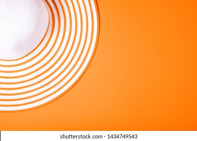 Summer and vacation concept. Top view of Straw striped hat on russet orange color background. Fasionable concept. Copy space.