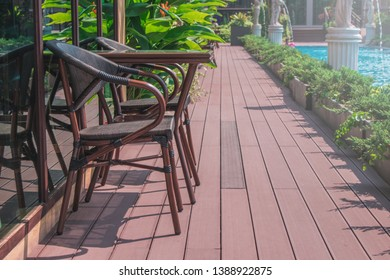 Summer Vacation Concept : Wooden weave brown chairs and table place on terrace beside swimming pool.