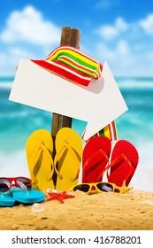 Summer vacation concept--Color Flipflops on a sandy ocean beach with arrow sign