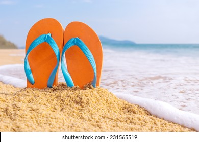 Summer vacation concept--Orange Flipflops on a sandy ocean beach