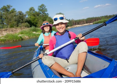 Summer vacation - Cute girl with mother kayaking on river.
