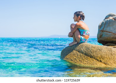 Summer vacation - Cute girl sitting on the stone in the transparent sea