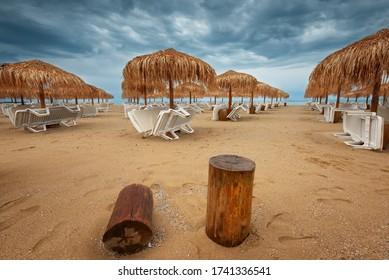 Sommerurlaubsziel. Strohschirme und Liegestühle am leeren Kiesstrand mit Meer im Hintergrund. Konzept für Urlaub und Tourismus. Liegestühle am Strand des Paradise. Sommer in Bulgarien.
