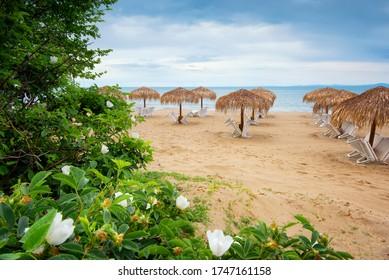 Sommerurlaubsziel. Strohsonnenschirme und Liegen am leeren Kieselstrand mit Meer im Hintergrund. Ferien- und Tourismuskonzept. Liegen am Paradise Beach. Sommer in Bulgarien.