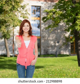 summer vacation, education, gesture and people concept - smiling teenage girl in casual clothes showing thumbs up over campus background
