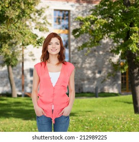summer vacation, education and people concept - smiling teenage girl in casual clothes over campus background