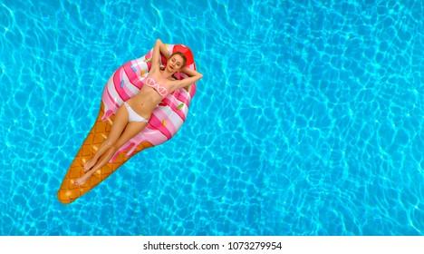 Summer Vacation. Enjoying suntan Woman in bikini on the inflatable mattress in the swimming pool.